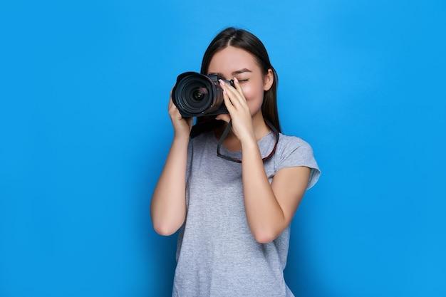 Jovem e bela fotógrafa asiática focada em uma câmera dslr profissional e na parede azul