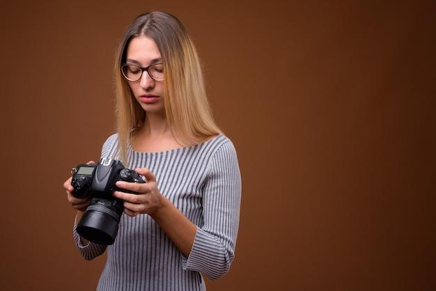 Jovem e bela fotógrafa segurando uma câmera dslr contra uma parede marrom