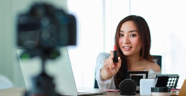 Jovem e bela garota asiática mostrando o batom para a câmera durante a transmissão ou gravação de vídeo sobre revista de cosméticos e blogueira de beleza. venda online e conceito de marketing.