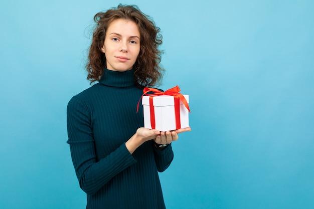 Jovem e bela garota caucasiana com cabelos cacheados mantém a caixa de presente branca com fita vermelha e sorrisos, retrato isolado em azul