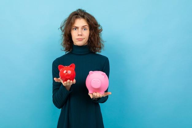 Jovem e bela garota caucasiana com cabelos cacheados mantém mealheiro de porco vermelho pequeno, mealheiro de porco rosa grande e sorrisos, retrato isolado em fundo azul