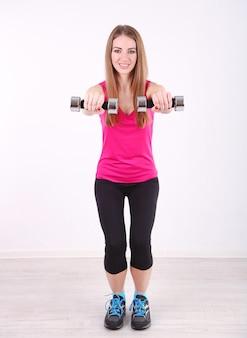 Jovem e bela garota fitness se exercitando com halteres na academia