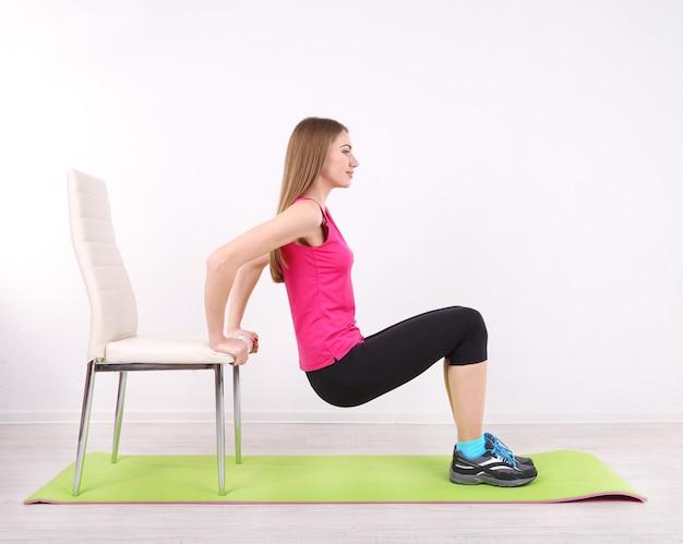 Jovem e bela garota fitness se exercitando no tapete verde, na academia