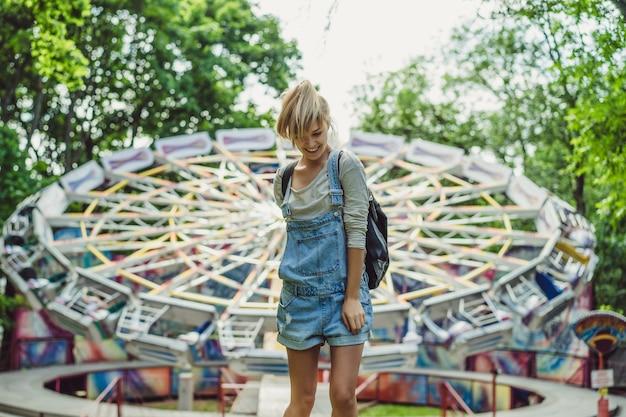 Jovem e bela garota loira em denim em geral com uma mochila posando em um parque de diversões