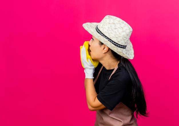Jovem e bela jardineira com avental de luvas de borracha e chapéu chamando alguém com as mãos em pé sobre a parede rosa