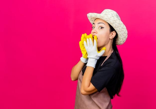 Jovem e bela jardineira com avental de luvas de borracha e chapéu cobrindo a boca com as mãos sendo surpreendida em pé sobre uma parede rosa