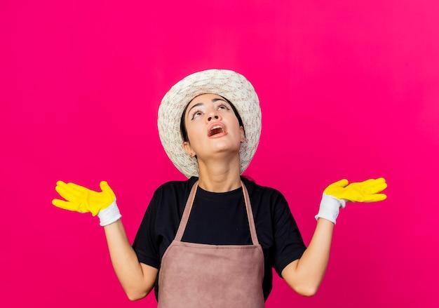 Jovem e bela jardineira com avental de luvas de borracha e chapéu, olhando para cima, confusa, abrindo os braços para os lados em pé sobre a parede rosa