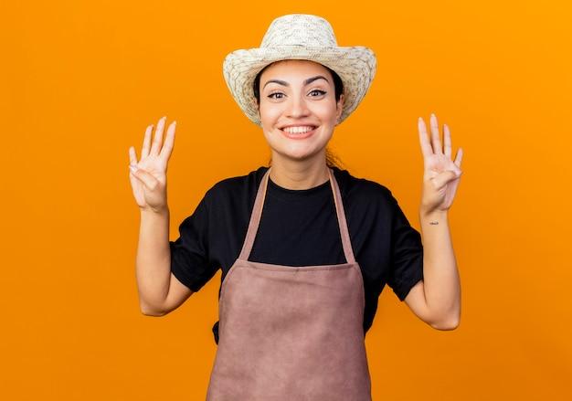 Jovem e bela jardineira com avental e chapéu aparecendo e apontando para cima com os dedos número oito em pé sobre a parede laranja