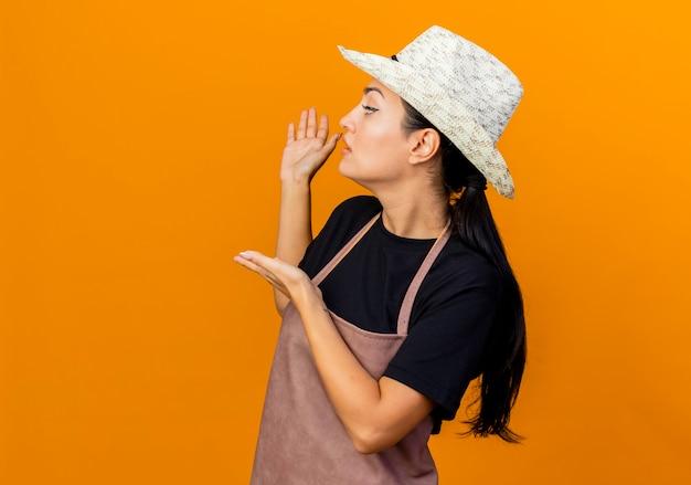 Jovem e bela jardineira com avental e chapéu apresentando algo com as mãos atrás dela em pé sobre uma parede laranja