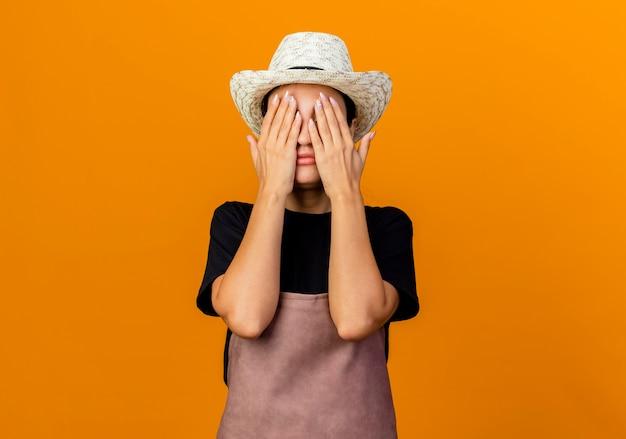 Jovem e bela jardineira com avental e chapéu cobrindo os olhos com as mãos em pé sobre uma parede laranja