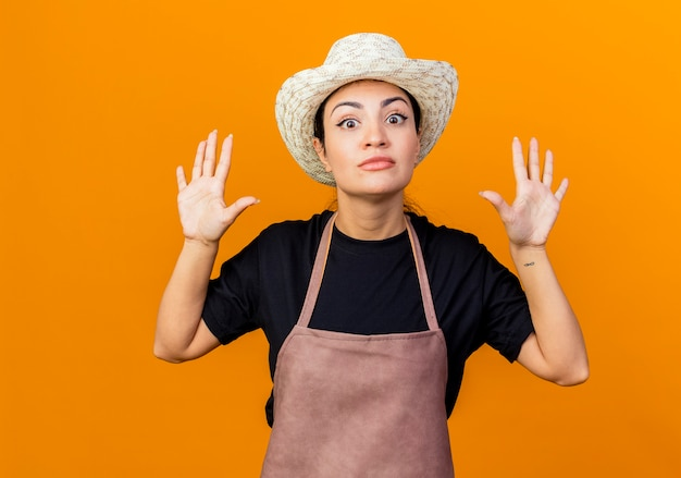 Jovem e bela jardineira com avental e chapéu levantando as mãos em sinal de rendição sendo surpreendida em pé sobre a parede laranja