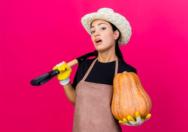 Jovem e bela jardineira com luvas de borracha, avental e chapéu segurando uma pá e uma abóbora, parecendo confusa em pé sobre uma parede rosa