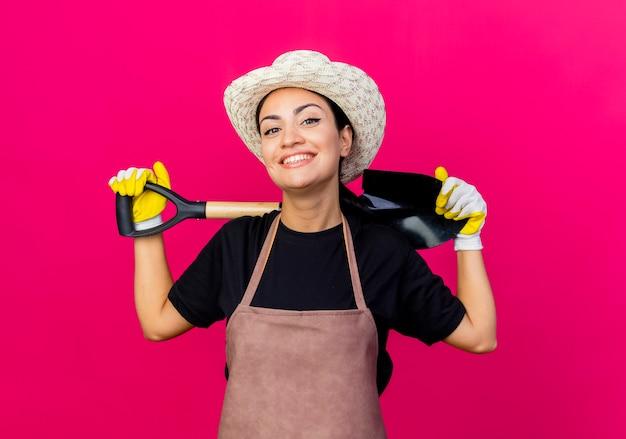 Jovem e bela jardineira com luvas de borracha, avental e chapéu segurando uma pá, olhando para a frente, sorrindo com uma cara feliz em pé sobre a parede rosa