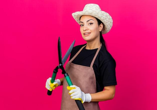 Jovem e bela jardineira com luvas de borracha, avental e chapéu segurando uma tesoura de sebes, olhando para a frente, sorrindo com uma cara feliz em pé sobre a parede rosa
