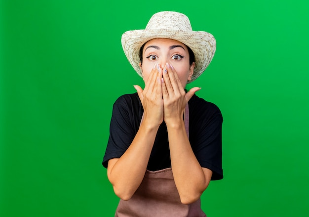 Jovem e bela jardineira de avental e chapéu olhando para a frente, cobrindo a boca com as mãos maravilhadas e surpresas em pé sobre a parede verde