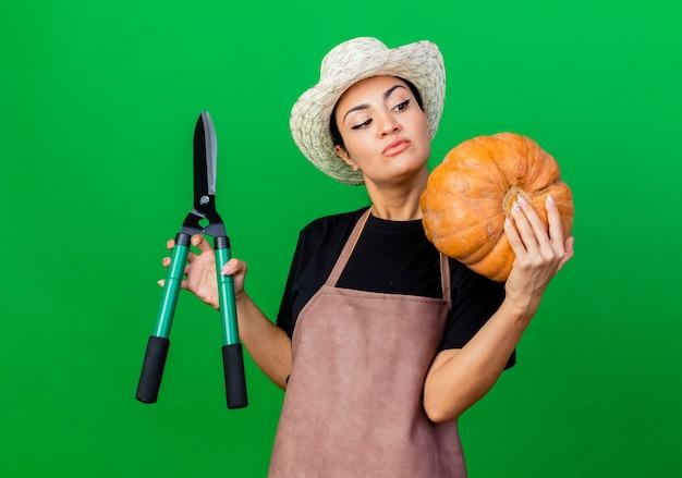 Jovem e bela jardineira de avental e chapéu segurando abóbora e cortador de cerca viva olhando para abóbora com cara séria em pé sobre a parede verde