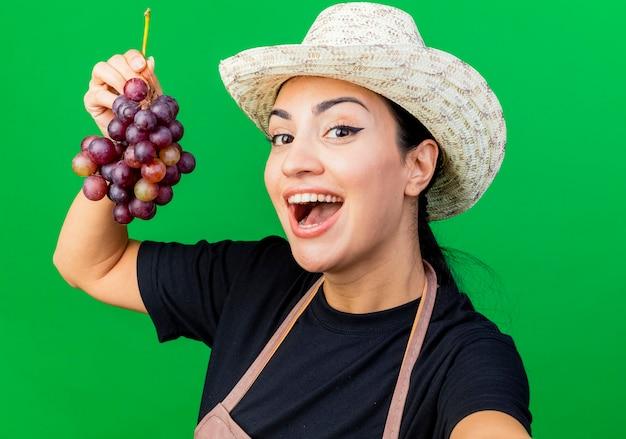 Jovem e bela jardineira de avental e chapéu segurando cacho de uva e sorrindo alegremente
