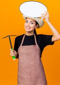 Jovem e bela jardineira de avental e chapéu segurando picareta e balão de fala em branco na cabeça sorrindo em pé sobre a parede laranja