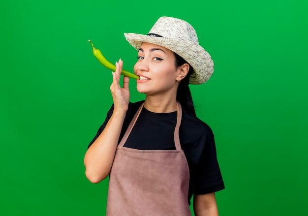 Jovem e bela jardineira de avental e chapéu segurando pimenta verde como um cigarro, sorrindo em pé sobre a parede verde