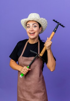 Jovem e bela jardineira de avental e chapéu segurando um mini ancinho olhando para a frente sorrindo alegremente em pé sobre a parede azul