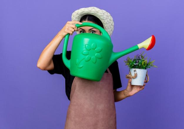 Jovem e bela jardineira de avental e chapéu segurando um regador e um vaso de planta em pé sobre a parede azul