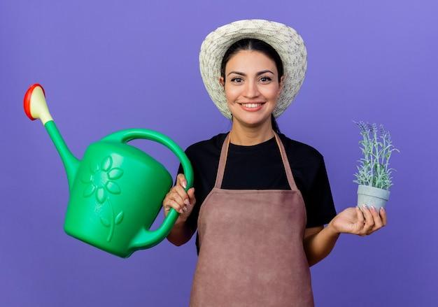 Jovem e bela jardineira de avental e chapéu segurando um regador e um vaso de planta olhando para a frente sorrindo em pé sobre a parede azul