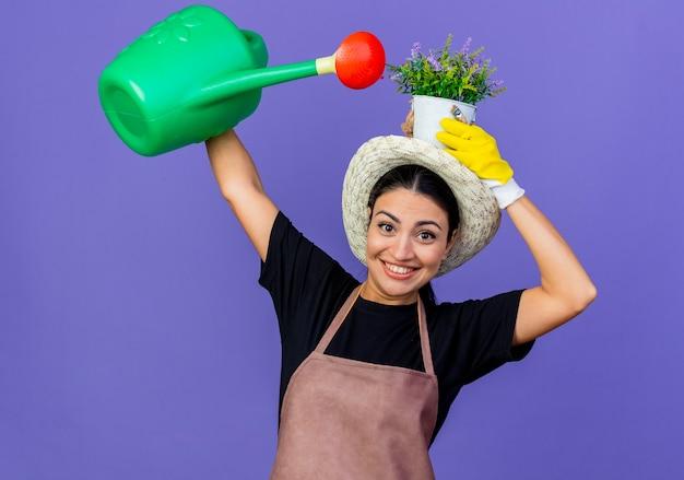 Jovem e bela jardineira de avental e chapéu segurando um regador e um vaso de plantas sorrindo alegremente se divertindo em pé sobre a parede azul