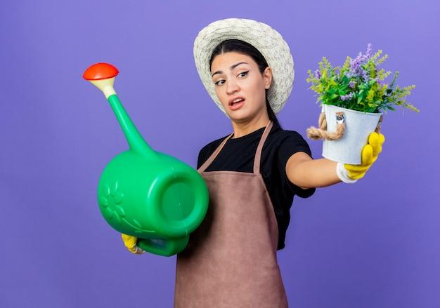 Jovem e bela jardineira de avental e chapéu segurando um regador mostrando uma planta em um vaso parecendo confusa em pé sobre a parede azul
