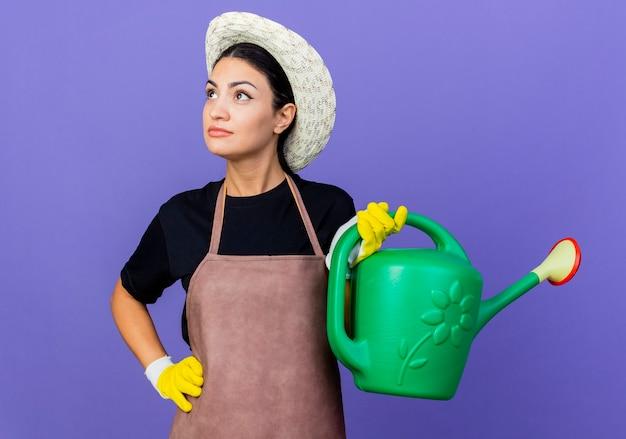 Jovem e bela jardineira de avental e chapéu segurando um regador olhando para o lado com expressão pensativa no rosto em pé sobre a parede azul
