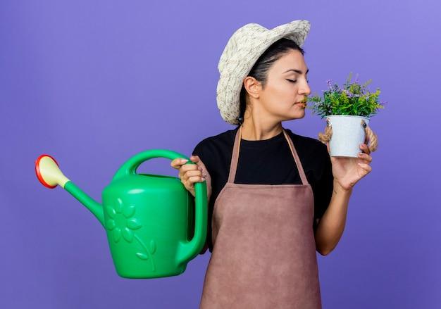 Jovem e bela jardineira de avental e chapéu segurando um regador olhando para um vaso em outro lado, em pé sobre a parede azul