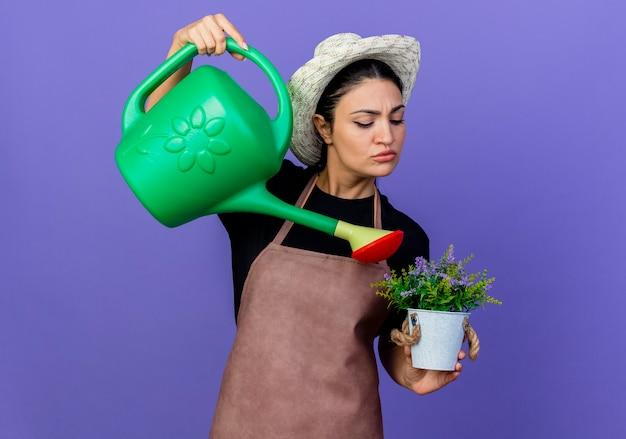 Jovem e bela jardineira de avental e chapéu segurando um regador, regando um vaso de planta em pé sobre a parede azul