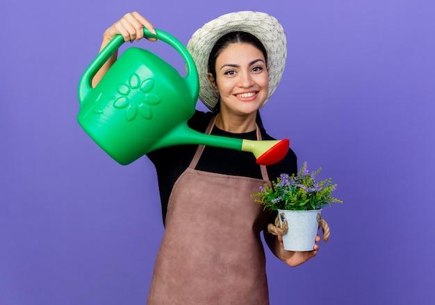 Jovem e bela jardineira de avental e chapéu segurando um regador, regando um vaso de planta sorrindo alegremente em pé sobre a parede azul