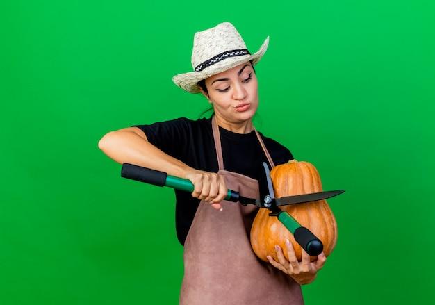 Jovem e bela jardineira de avental e chapéu segurando uma abóbora e um cortador de cerca viva olhando para ela com uma cara séria em pé sobre a parede verde
