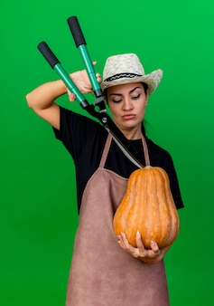 Jovem e bela jardineira de avental e chapéu segurando uma abóbora e um cortador de cerca viva olhando para ela com uma cara séria