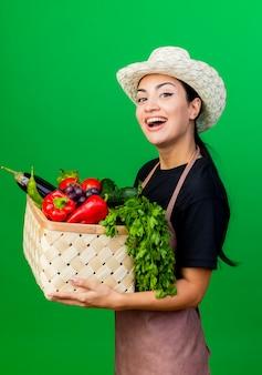 Jovem e bela jardineira de avental e chapéu segurando uma cesta cheia de vegetais e sorrindo com uma cara feliz