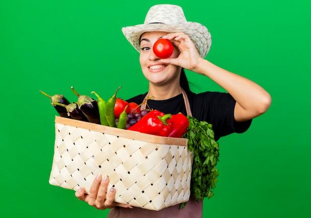Jovem e bela jardineira de avental e chapéu segurando uma cesta cheia de vegetais e tomate perto do olho, sorrindo em pé sobre a parede verde