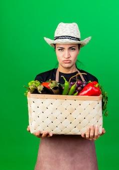 Jovem e bela jardineira de avental e chapéu segurando uma cesta cheia de vegetais, olhando para a frente com uma cara séria e descontente em pé sobre a parede verde