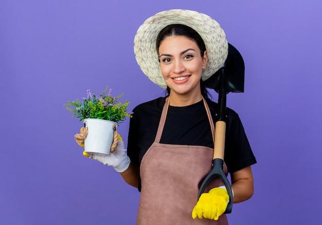 Jovem e bela jardineira de avental e chapéu segurando uma pá e um vaso de planta sorrindo confiante em pé sobre a parede azul