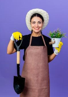 Jovem e bela jardineira de avental e chapéu segurando uma pá e um vaso de plantas olhando para frente com um sorriso no rosto em pé sobre a parede azul