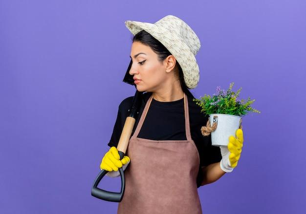 Jovem e bela jardineira de avental e chapéu segurando uma pá e um vaso de plantas, parecendo confiante em pé sobre a parede azul