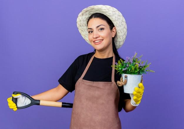 Jovem e bela jardineira de avental e chapéu segurando uma pá, mostrando um vaso de planta sorrindo alegremente em pé sobre a parede azul