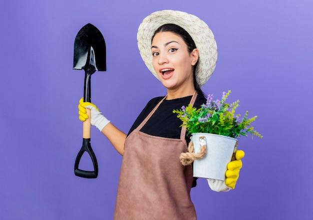 Jovem e bela jardineira de avental e chapéu segurando uma pá, mostrando um vaso de planta sorrindo com uma cara feliz em pé sobre a parede azul
