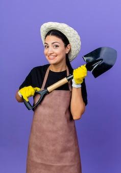 Jovem e bela jardineira de avental e chapéu segurando uma pá, olhando para a frente, sorrindo alegremente em pé sobre a parede azul