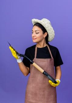 Jovem e bela jardineira de avental e chapéu segurando uma pá olhando para ela com um sorriso no rosto em pé sobre a parede azul