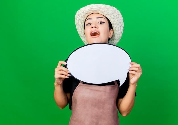 Jovem e bela jardineira de avental e chapéu segurando uma placa de balão em branco, espiando surpresa em pé sobre a parede verde