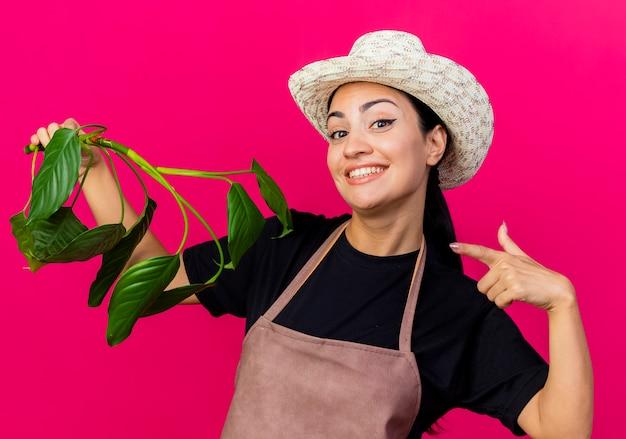 Jovem e bela jardineira de avental e chapéu segurando uma planta apontando com o dedo indicador sorrindo em pé sobre a parede rosa