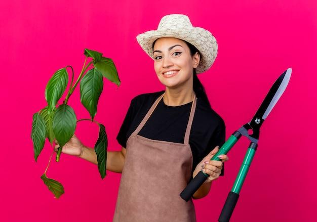 Jovem e bela jardineira de avental e chapéu segurando uma planta e um cortador de cerca viva sorrindo com uma cara feliz