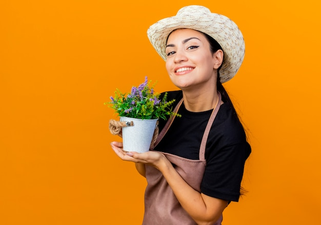 Jovem e bela jardineira de avental e chapéu segurando uma planta em um vaso, olhando para a frente, sorrindo em pé sobre a parede laranja