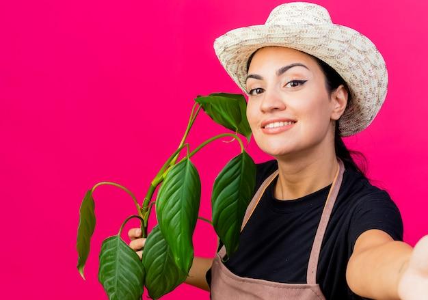 Jovem e bela jardineira de avental e chapéu segurando uma planta olhando para a frente sorrindo com uma carinha feliz em pé sobre a parede rosa