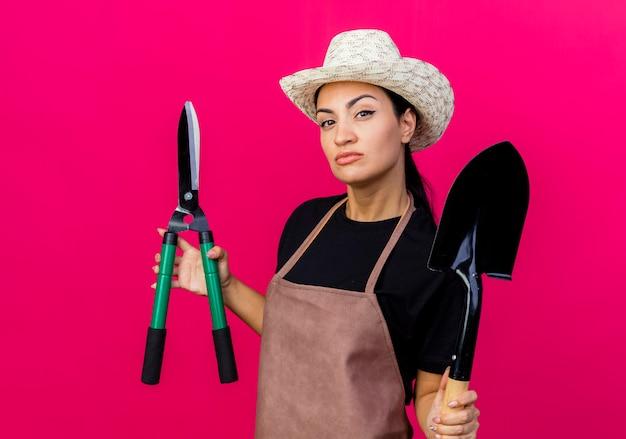 Jovem e bela jardineira de avental e chapéu segurando uma tesoura de cerca viva e uma pá olhando para frente com uma cara séria em pé sobre a parede rosa